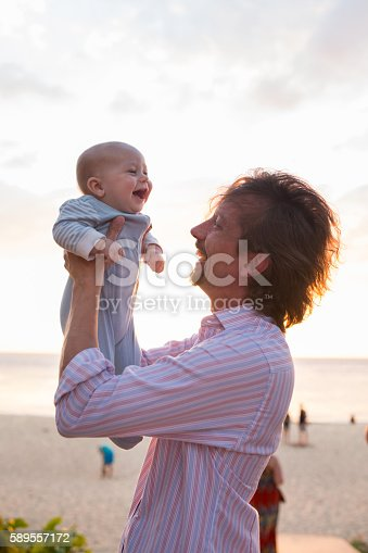 istock Cheerful baby and father having fun during summer. 589557172
