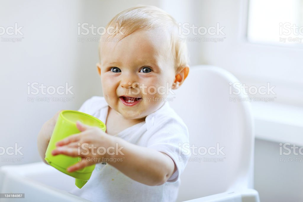 Cheerful baby girl sitting in chair and holding cup stock photo