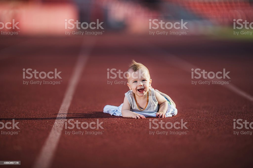 Cheerful baby on a sports track. stock photo