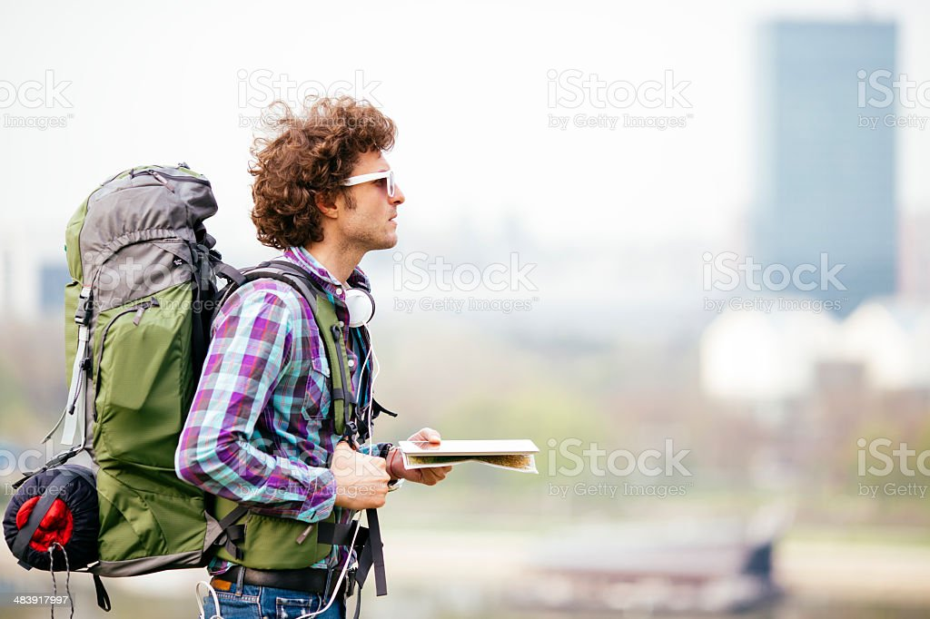 Cheerful Backpacker Holding Map. stock photo