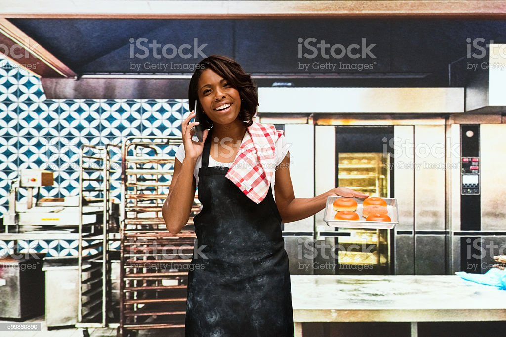 Cheerful baker on phone and  holding bread stock photo