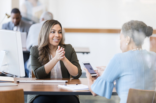 A confident female bank employee explains a convenient banking mobile app to a female customer. The customer is reviewing the app on her smartphone