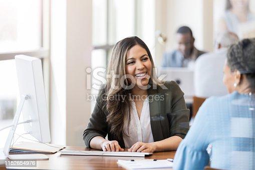 istock Cheerful bank employee opens account for customer 1152654976