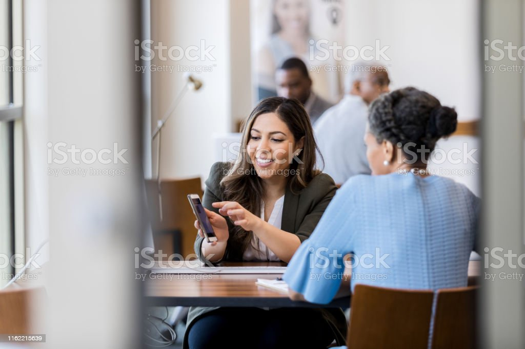 Cheerful bank employee shows customer banking app - Royalty-free Adulto Foto de stock
