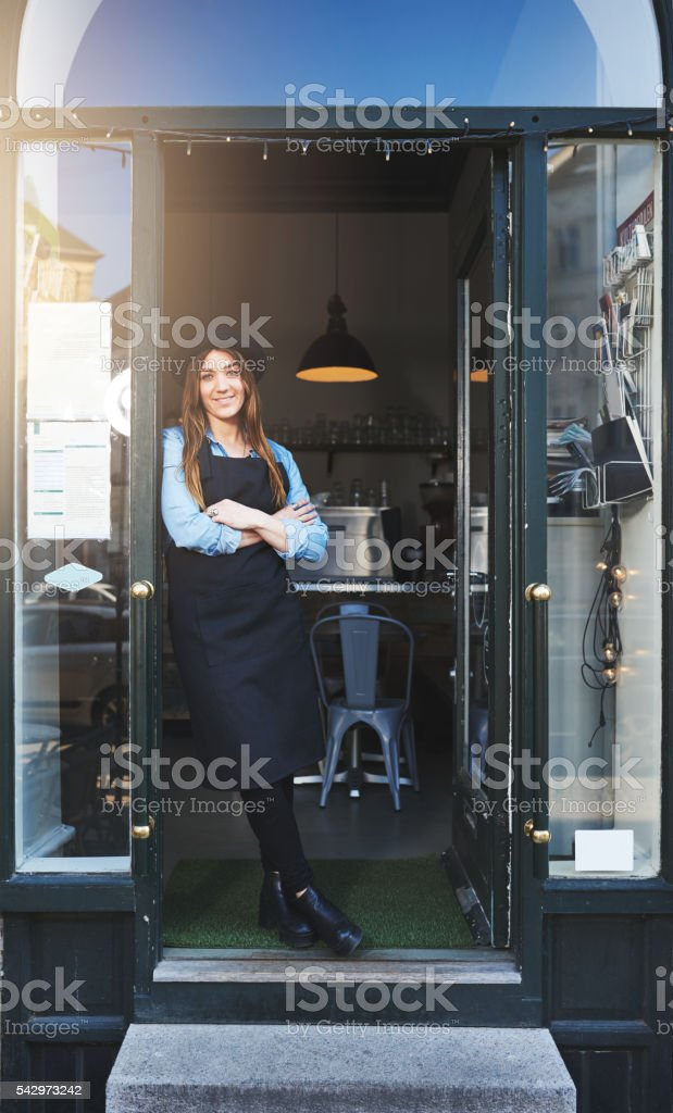 Cheerful barista leaning against doorway in cafe stock photo