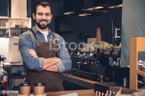 istock Cheerful barista working in cafe 874875396