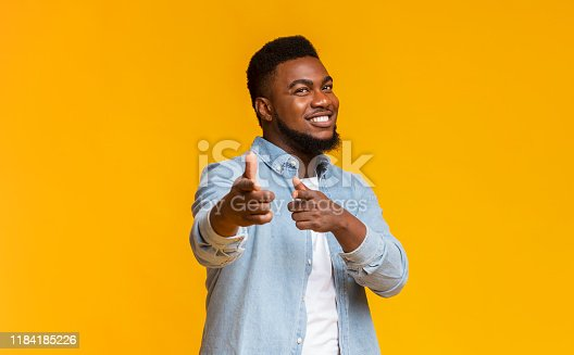 istock Cheerful bearded black guy pointing fingers at camera 1184185226