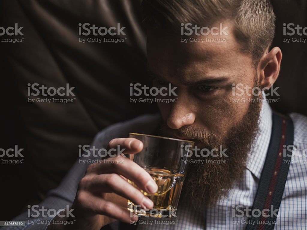 Cheerful bearded businessman is drinking expensive whisky stock photo