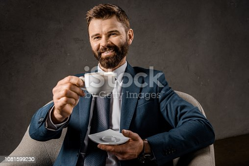 1081599130 istock photo cheerful bearded businessman showing cup of coffee 1081599230