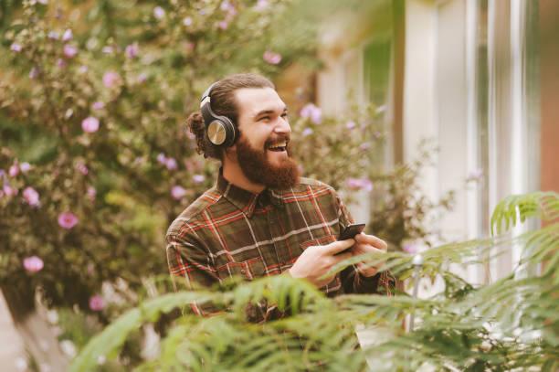 glad skäggiga hipster man leende och lyssnar musik på trådlösa hörlurar - happy indie pop bildbanksfoton och bilder