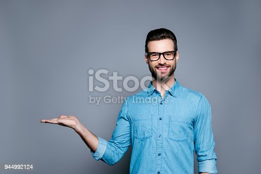 istock Cheerful bearded man in glasses making advertisement of new product 944992124
