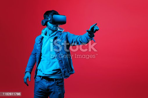 istock Cheerful bearded man trying VR headset and exploring another world in studio on red background in neon light. Smartphone using with VR headset. 1152611766