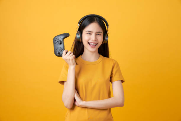 Cheerful beautiful Asian woman in casual yellow t-shirt and playing video games using joysticks with headphones on orange background. stock photo