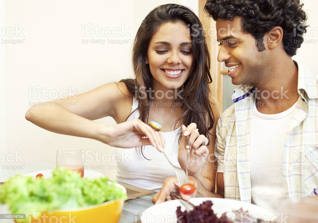 Cheerful beautiful brazilian couple having lunch at home. royalty-free stock photo