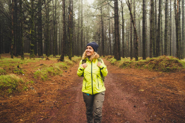 Cheerful beautiful caucasian middle age woman doing trekking outdoor activity in the forest ina rainy day - adventure lifestyle for people love freedom and independence - beautiful nature concept stock photo