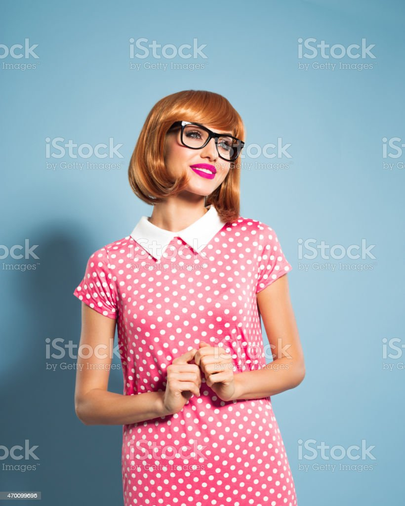 Cheerful beautiful red hair young woman wearing polka dot dress stock photo
