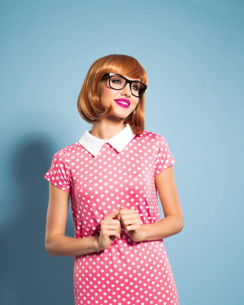 fröhlich schöne rote haare junge frau mit kleid mit pünktchenmuster - moderne 50er jahre mode stock-fotos und bilder