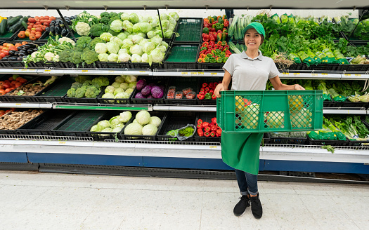 Cheerful Beautiful Sales Clerk Holding A Basket With Vegetables And Fruits  Facing Camera Smiling Standing In Front Of A Refrigerated Section Stock  Photo - Download Image Now - iStock