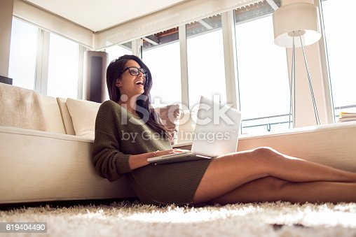 618976144istockphoto cheerful beautiful young woman using her laptop 619404490