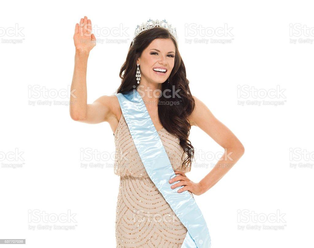 Cheerful beauty queen waving hand stock photo