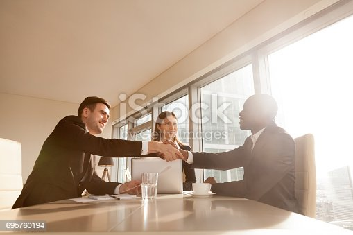istock Cheerful black and white businessmen shaking hands at multi-ethnic meeting 695760194