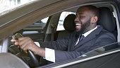 Cheerful black businessman sitting in luxury automobile, test drive, transport