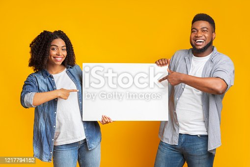 1159989540 istock photo Cheerful black couple holding and pointing at blank advertisement placard 1217794152