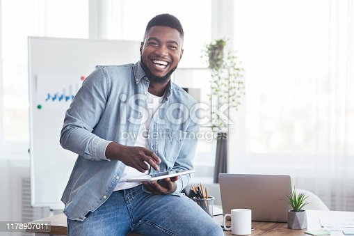 Work with fun. Portrait of cheerful black employee using digital tablet in modern office and laughing out loud
