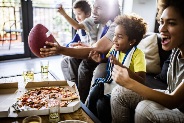 Cheerful black family cheering while watching rugby match on TV at home. Young joyful black family having fun while cheering for their favorite American football team at home. Focus is on girl. american football sport stock pictures, royalty-free photos & images