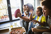 istock Cheerful black family cheering while watching rugby match on TV at home. 1224519653