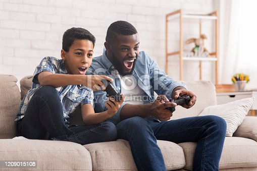 Leisure With Dad. Cheerful Black Father And Son Competing With Each Other In Video Games, Using Joysticks, Having Fun At Home, Free Space