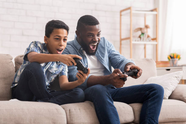Cheerful Black Father And Son Competing In Video Games At Home Leisure With Dad. Cheerful Black Father And Son Competing With Each Other In Video Games, Using Joysticks, Having Fun At Home, Free Space computer games stock pictures, royalty-free photos & images
