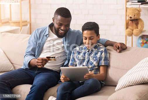 Cheerful Black Father Shopping Online With His Son Using Digital Tablet At Home, Entering Credit Card Security Code