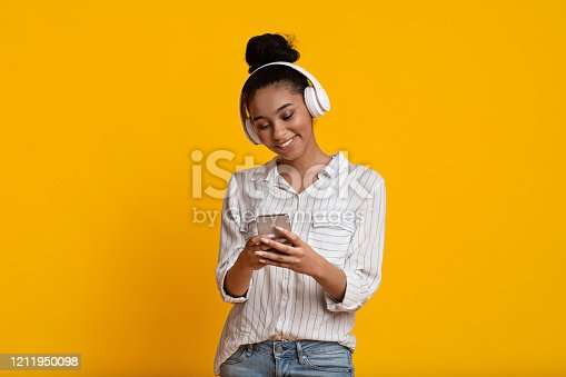 istock Cheerful Black Girl In Wireless Headphones Listening Music On Smartphone 1211950098
