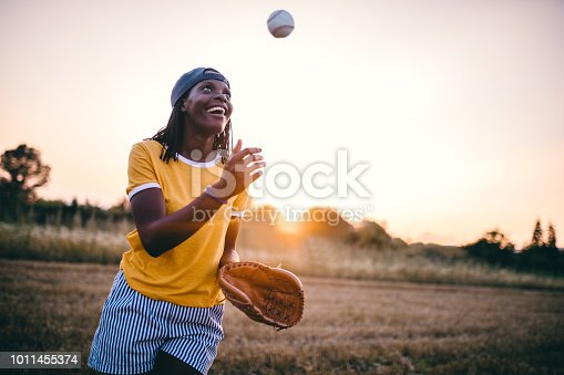 Gorgeous and fashionable black girl playing baseball outdoors in nature.