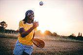 Cheerful black girl playing baseball