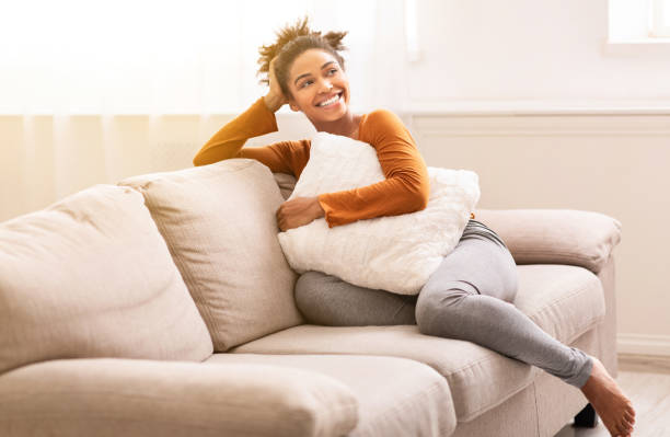 Cheerful Black Girl Sitting On Couch Relaxing At Home stock photo