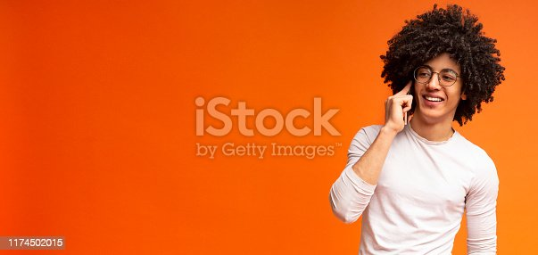 istock Cheerful black guy enjoying mobile talk with friend 1174502015