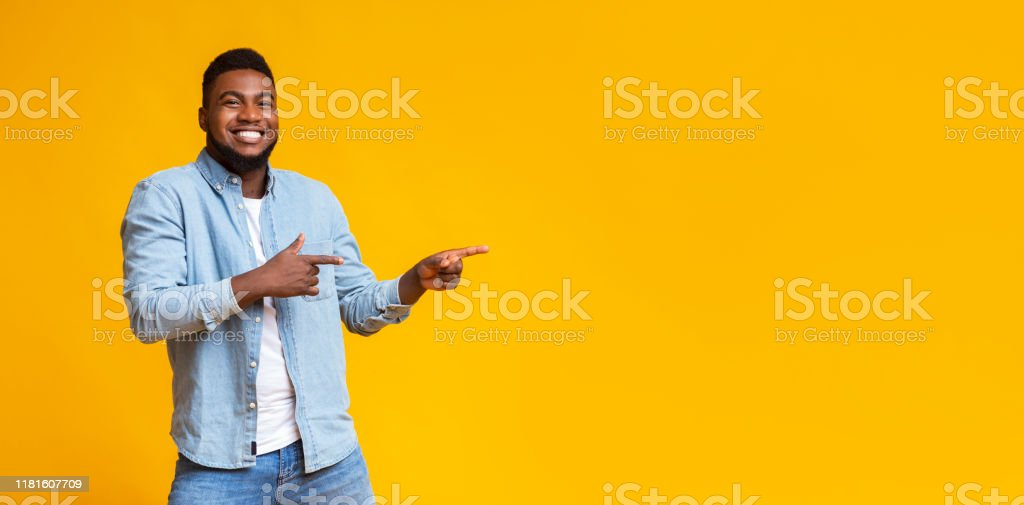 Cheerful black guy pointing two fingers aside at copy space Cool offer. Cheerful african american man pointing two fingers aside at copy space on yellow studio background, panorama Adult Stock Photo