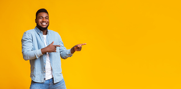 Cheerful Black Guy Pointing Two Fingers Aside At Copy Space Stock Photo - Download Image Now