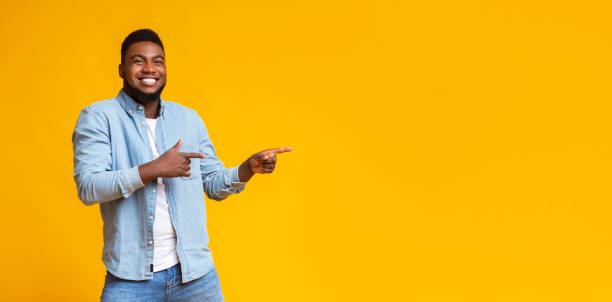 Cheerful black guy pointing two fingers aside at copy space Cool offer. Cheerful african american man pointing two fingers aside at copy space on yellow studio background, panorama excited stock pictures, royalty-free photos & images