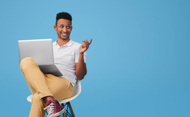 Cheerful black hipster with laptop stock photo