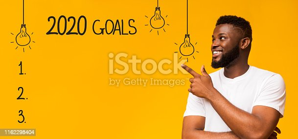 istock Cheerful black man pointing at checklist with 2020 goals 1162298404