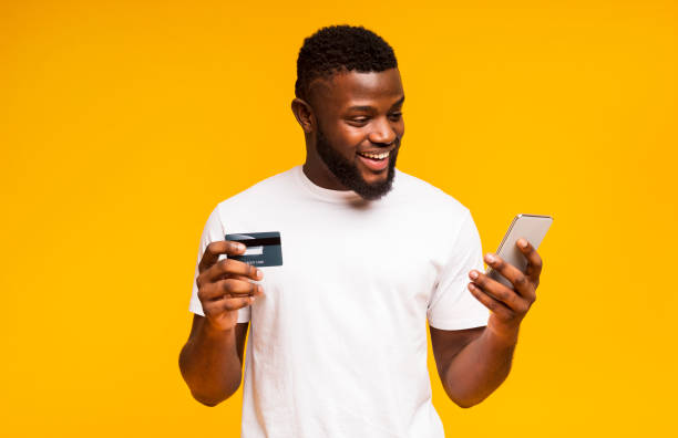Cheerful black man using credit card and smartphone for purchasing online Online payment. Cheerful black man using credit card and smartphone for purchasing goods phone charging stock pictures, royalty-free photos & images