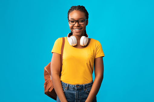 Cheerful Black Millennial Girl Smiling Standing With Backpack In Studio