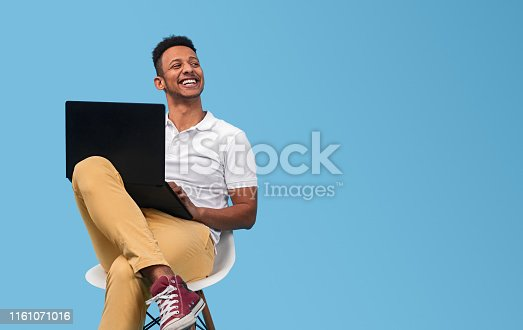 Young African American man smiling and looking at empty space while sitting on chair and using laptop against blue background