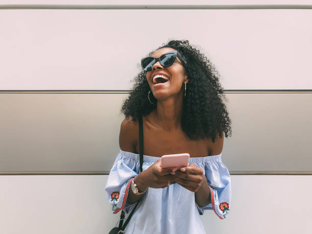 Cheerful black woman with mobile phone stock photo