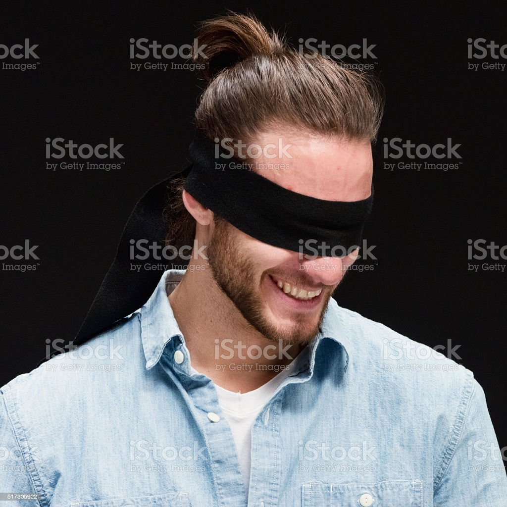 Cheerful blindfold man laughing stock photo