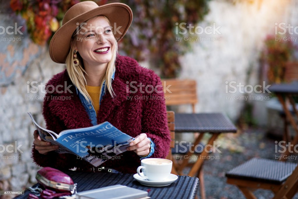 Portrait of excited young woman reading journal about traveling with...