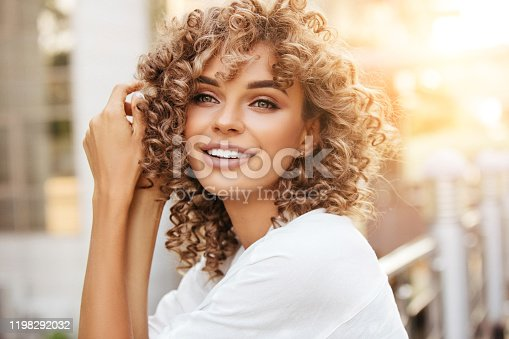 Cheerful blond woman smiling and enjoying outdoor during a beautiful sunset